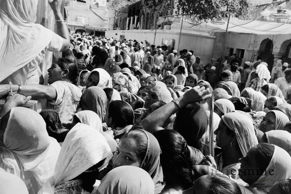 Les femmes font la queue, ici, à Amritsar, pour avoir la possibilité de se baigner dans les eaux sacrées entourant le temple d'or à Amritsar en Inde.