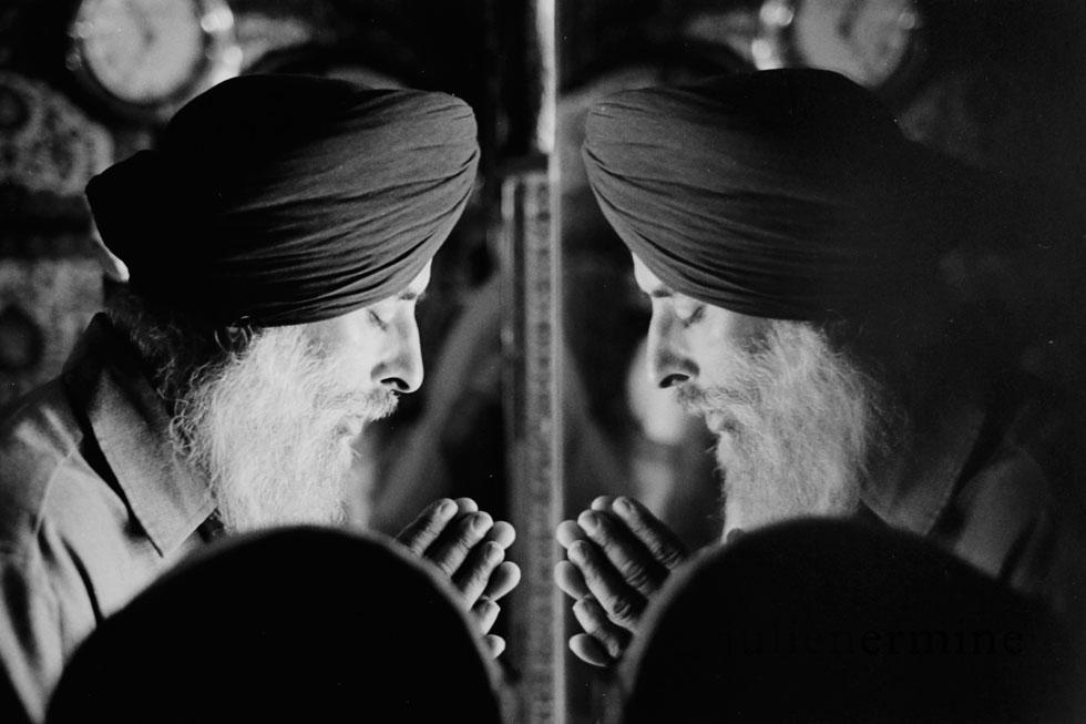 Priere D'un sikh en face d'un texte sacrée à l'entrée de la passerelle menant au temple d'Or à Amritsar en Inde.