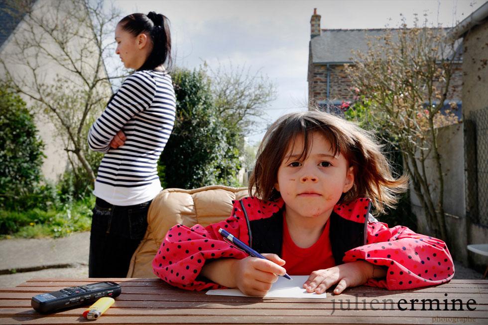 Dans le jardin d'une maison squattée, cette jeune fille apprend le français, et tente de faire ses devoirs.