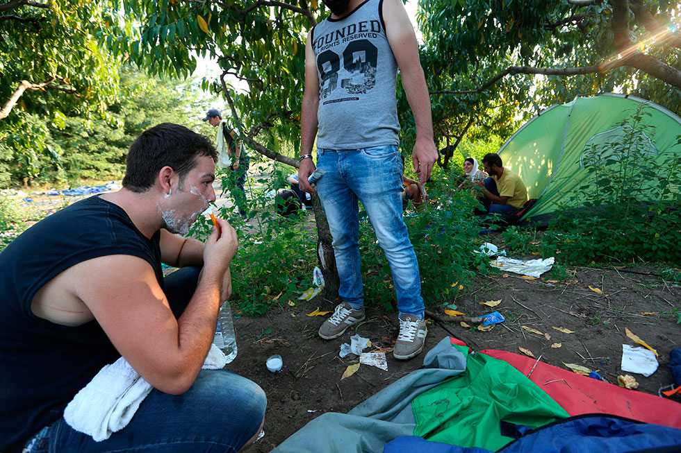 18H01 - Quelques heures avant de tenter de passer illégalement en Hongrie, ce Syrien occupe son temps en faisant sa toilette. La nuit à venir sera longue.