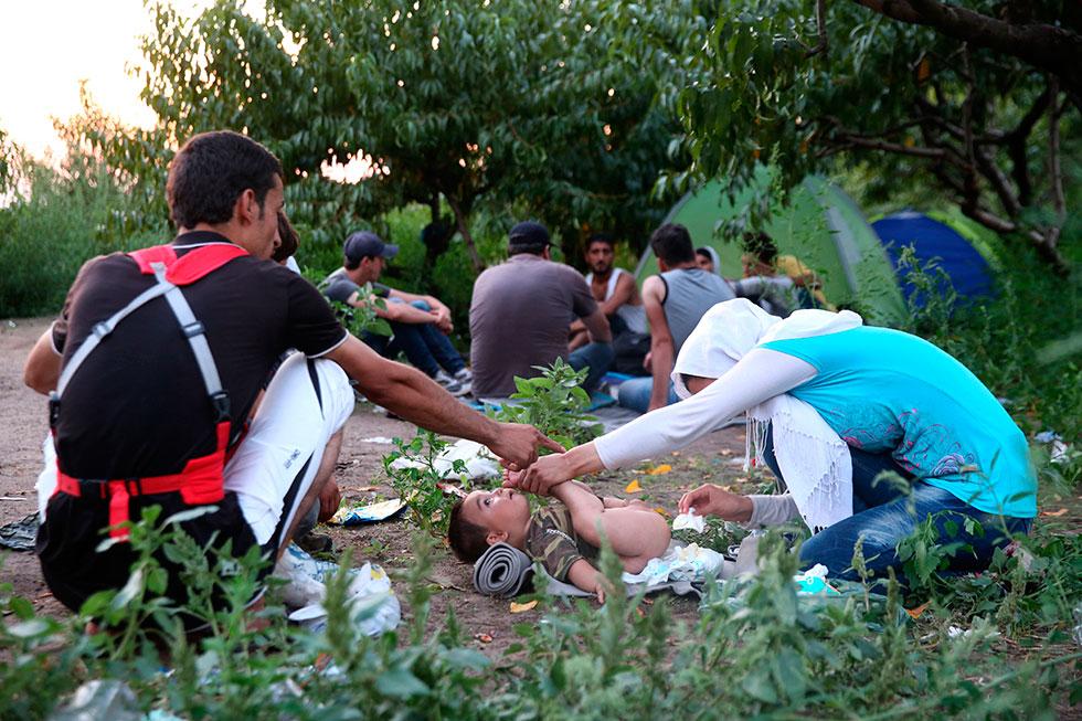 19H25 - Cette famille syrienne change une dernière fois la couche de leur bébé avant de passer la frontière serbo hongroise protégée par des barbelés. Il décideront finalement de ne pas accompagner le groupe pour cette nuit cruciale.