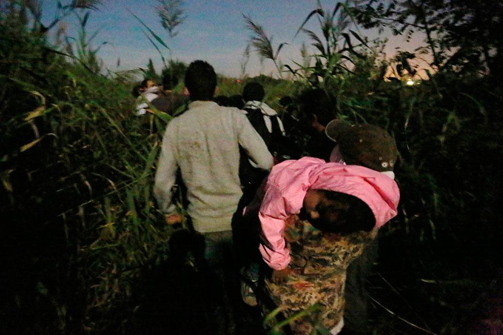 23H44 - Trop fatiguée, cette petite fille s'est endormie dans les bras de sa mère alors que le groupe poursuit son chemin à travers les épis de maïs en direction des barbelés.