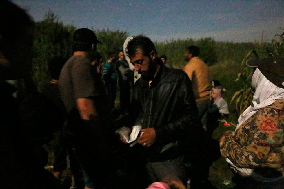 00H08 - Ce Syrien sort de l'argent pour le donner au passeur serbe. Ce dernier coupera les fils barbelés afin que lui et les autres puissent passer en Hongrie au petit matin. Le tarif : 500 euros pour couper les barbelés et y laisser passer 30 personnes.