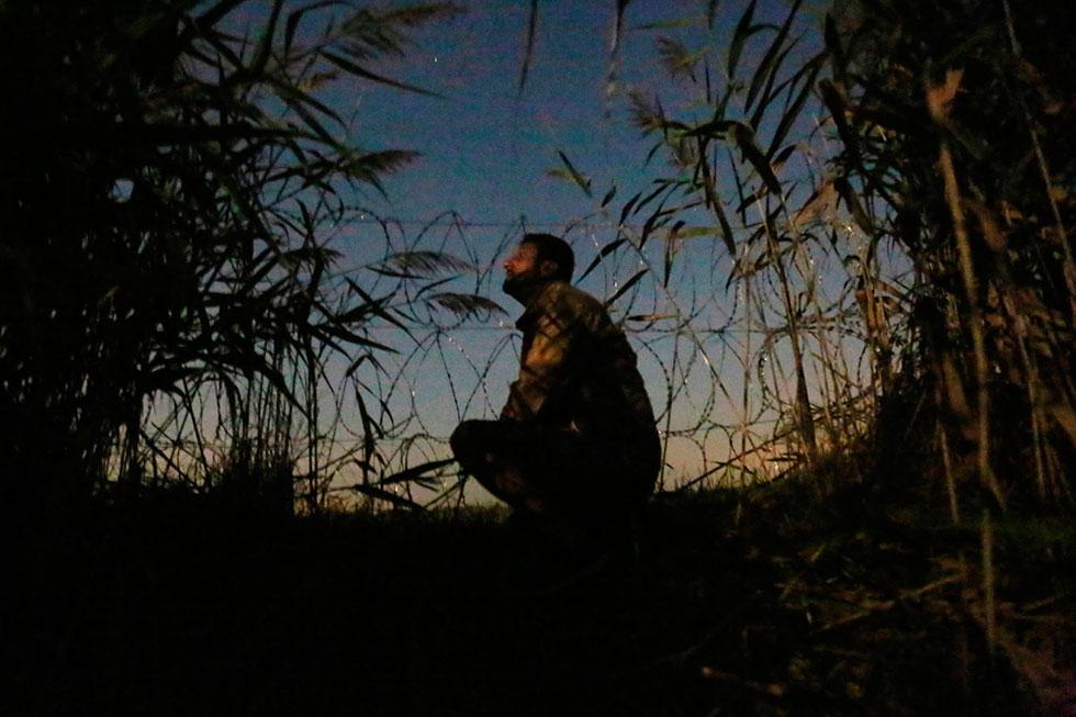 3H04 - En pleine nuit, ce migrant syrien guette la police toute proche aux abords de la clôture. La première tentative de passage illégal sera un échec. Il est resté caché dans les roseaux pendant 2 heures avant que police ne nous découvre.