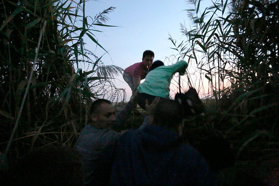5H15 - Le groupe de Syriens s'apprête enfin à passer la frontière entre la Serbie et la Hongrie au petit matin. Le passeur serbe vient tout juste de couper la clôture barbelée.