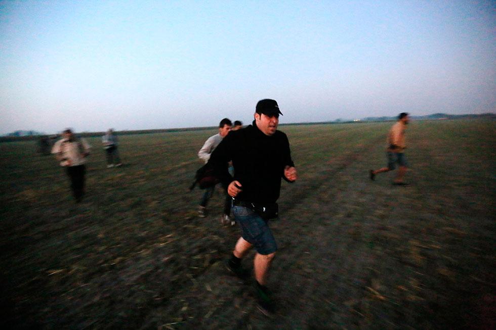 5H18 - Quelques minutes après avoir passé la frontière serbo-hongroise illégalement, ils courent vers leur liberté au petit matin dans les champs de maïs.