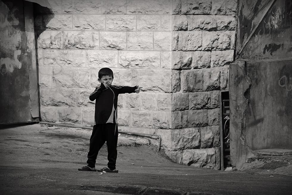 En face d'un check–point, les plus jeunes miment et reproduisent ce que font les plus grands.