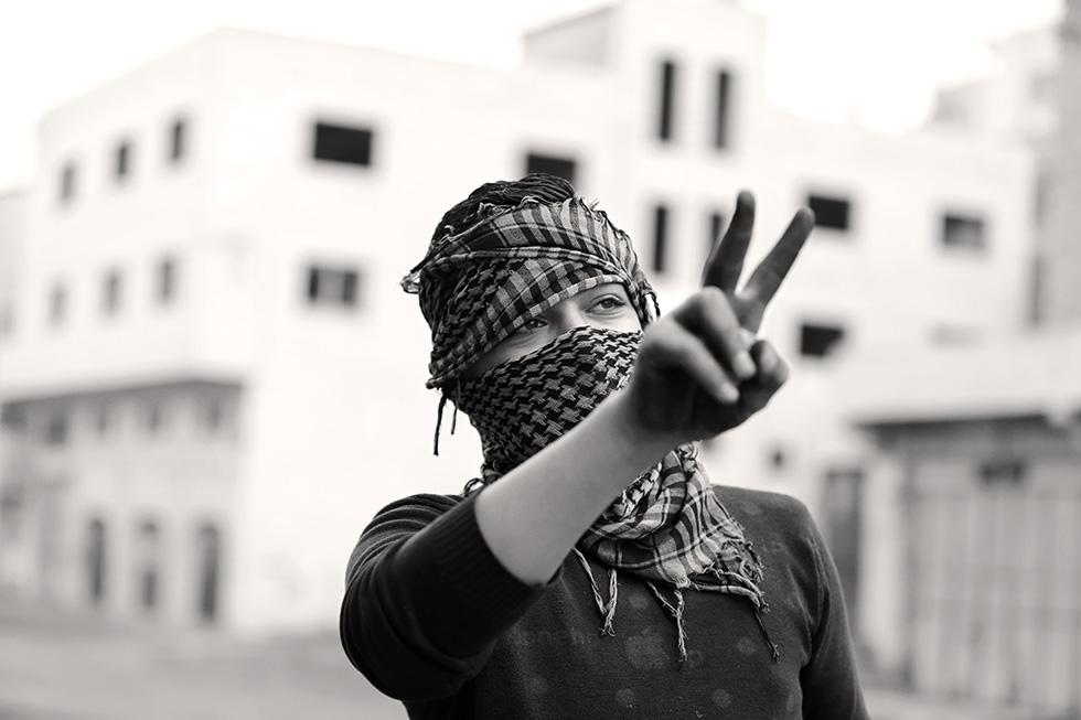 Ce jeune palestinien d'Hébron nargue des militaires israéliens sur un check-point qui sépare une colonie juive du quartier musulman.