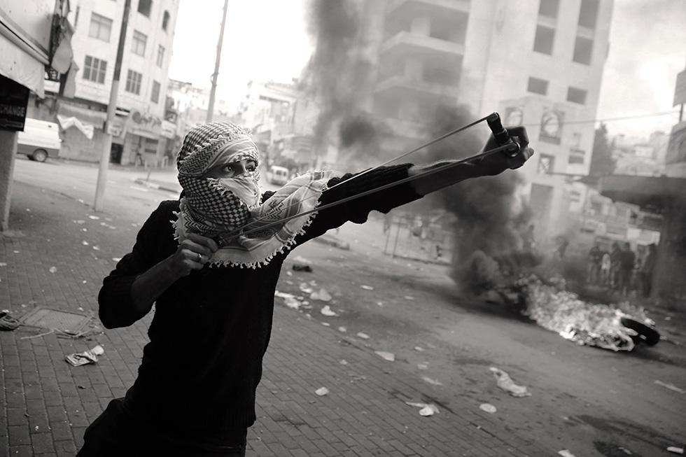 En représaille de l'agitation quotidienne, les rues du centre ville se transforment en zone de guerilla. Cet adolescent tire des billes sur les snipers postés sur les toits.