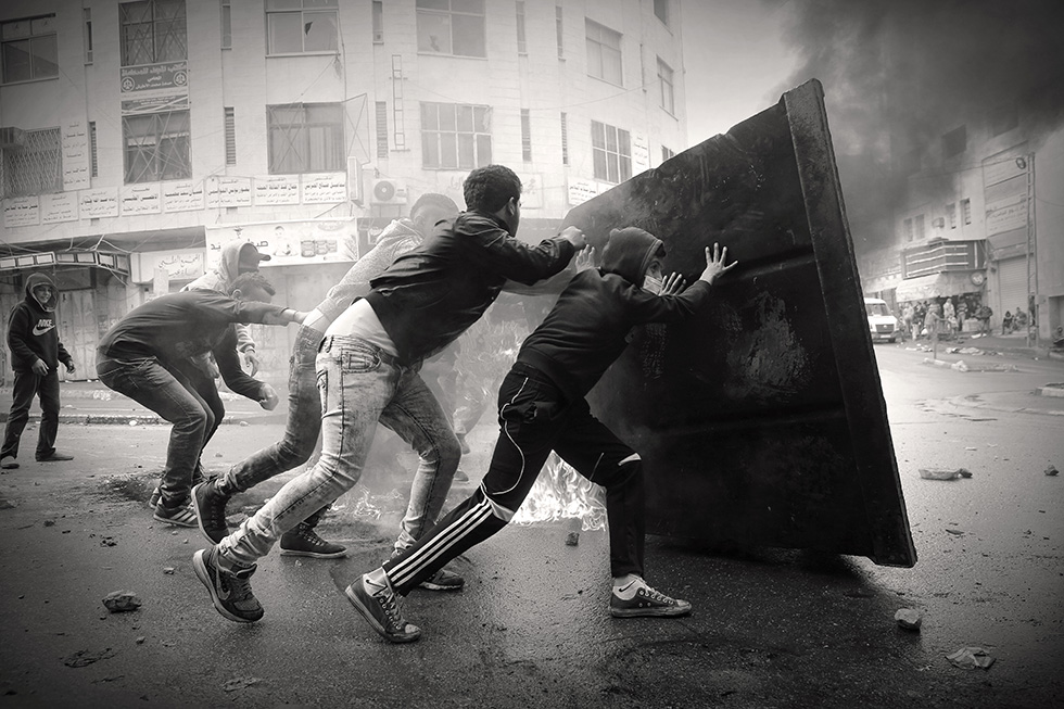 Ces adolescents avancent comme ils peuvent en direction des combats, à l'abri des tirs, cachés derrière une grande poubelle métallique à laquelle ils ont mis le feu.