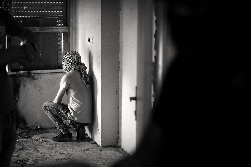 Un combattant observe les mouvements des troupes israéliennes dans les étages d'un immeuble délabré́ du centre-ville d'Hébron.