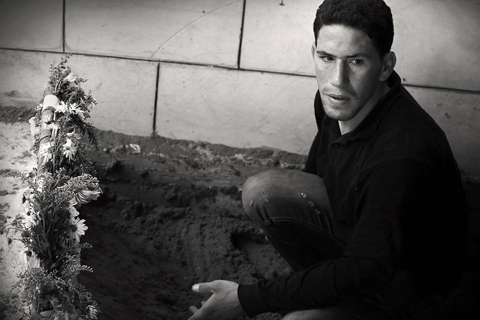 Sous cette couche de sable se trouve le corps du frère de ce jeune homme, décédé́ quelques jours plus tôt dans les affrontements. Il vient d'etre enterré quelques minutes plus tôt.