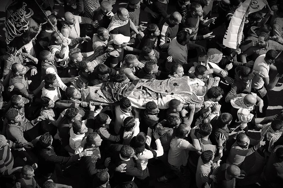 Le cortège funéraire de cinq martyrs, portés à dos d'homme, avance dans les rues, jusqu'au lieu où se déroulera l'enterrement. Une foule de 50000 personnes accompagne ses défunts dans ce jour de deuil.