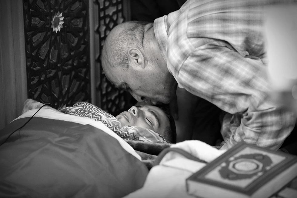 Un père embrasse une dernière fois son fils, mort en martyr dans la mosquée Hussein, bondée.