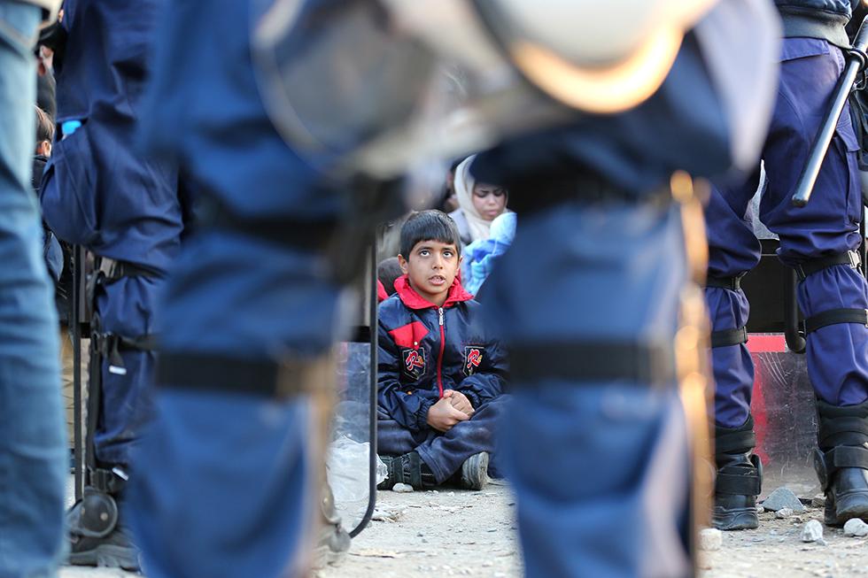 Ce jeune Irakien attend son tour avec sa famille, bien encadré par la police grecque, pour franchir légalement cette frontière entre la Grèce et la Macédoine.