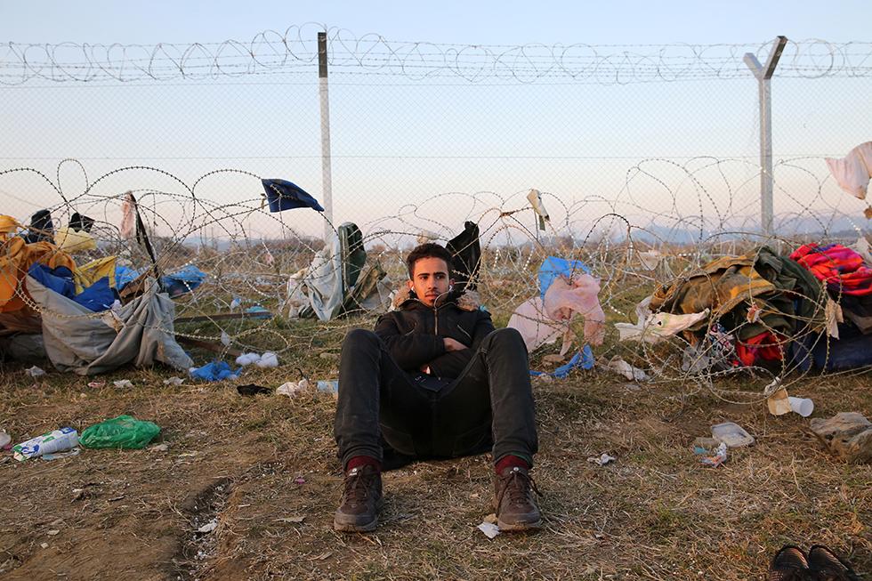 Lui, est Irakien. Il passe le temps les écouteurs sur les oreilles dans ce décor. Entouré de murs métalliques et de barbelés il attend une régularisation de sa situation.