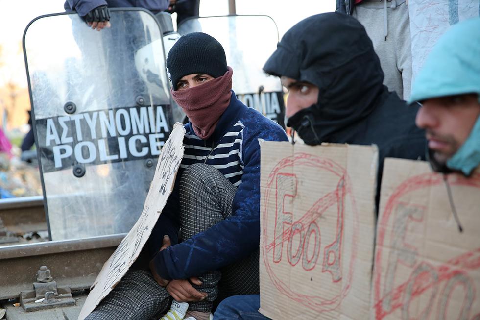 Assis devant les grillages de la frontière, certains migrants manifestent dans le silence.