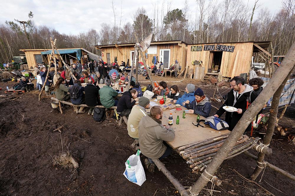 le moment est convivial lors du déjeuner sur l'un des sites de cabanes de la ZAD.