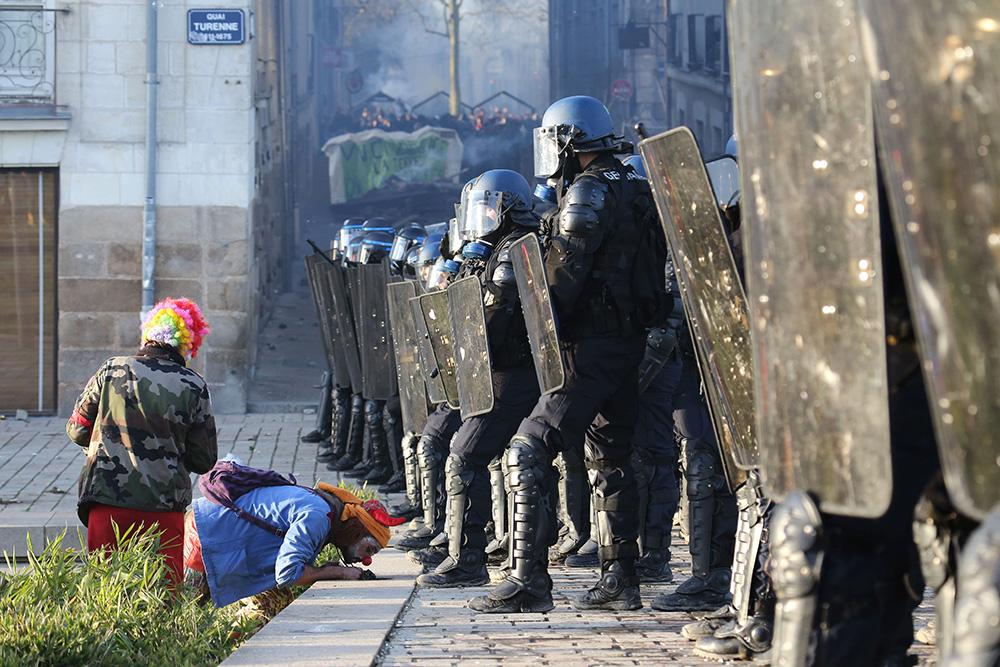 La tension monte, les premières echaufourés éclatent. les CRS se sont positionnés dans les rues du centre ville de Nantes, prêts à intervenir. Pendant ce temps là, les clowns manifestants armés de leur non violence et de leur bonne humeur offre des fleurs