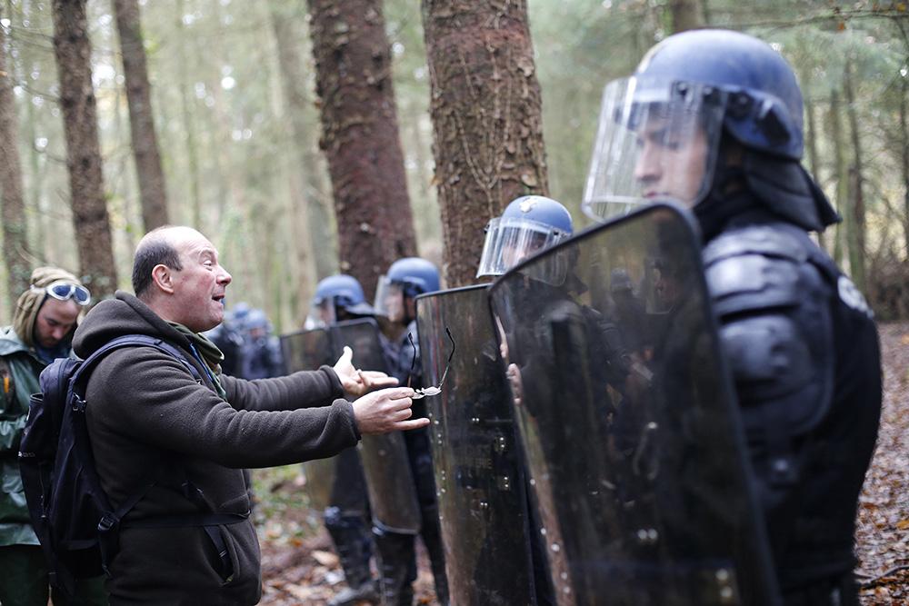 Dans les bois de notre dame des landes, un manifestant prend à partie les representants de la lois. Il leur fait en quelque sorte la lecon. peu de temps apres les forces de l'ordres emploieront la maniere fortes pour tenter d'expulser les recalcitrants et
