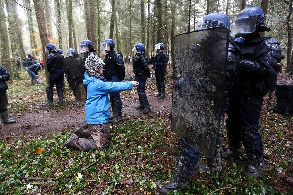 ce manifestant tend de lui même ses mains afin d être menotté alors que les représentants de l'ordre s'efforcent de maintenant leur ligne face a des centaines d'autres opposants moins pacifiques.